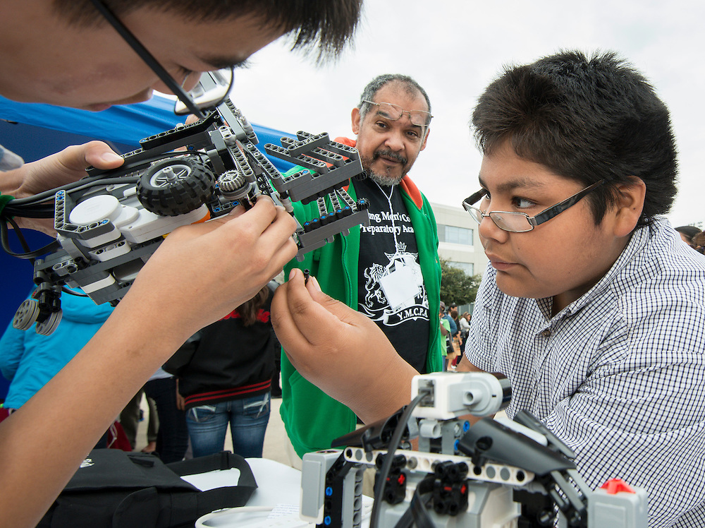 Students work on one of Young Men's College Preparatory Academy's robots at the When I Grow Up fair, March 8, 2014.
