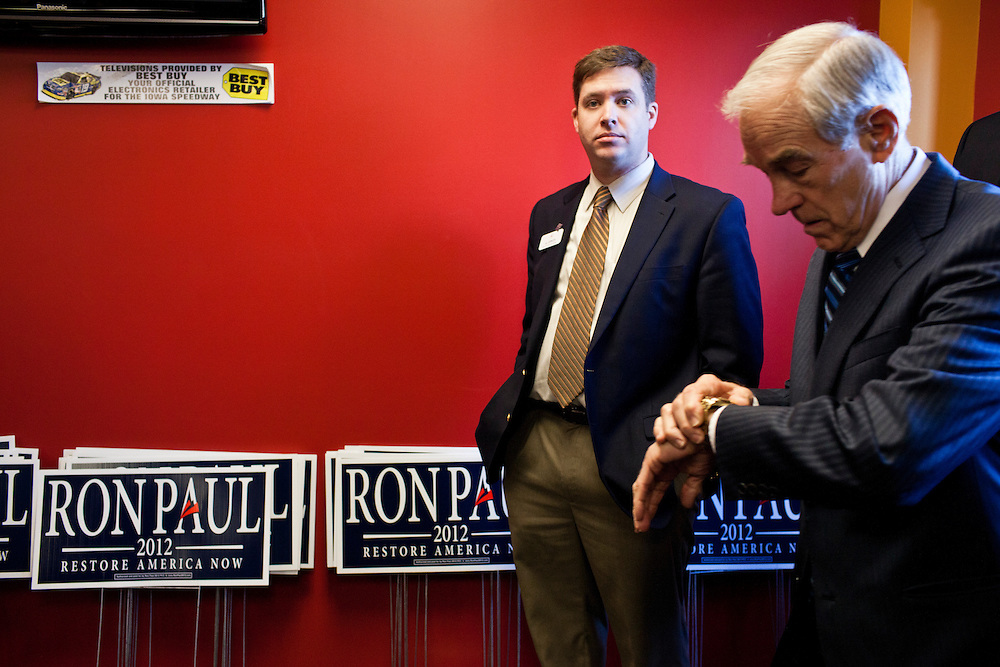 Republican presidential candidate Ron Paul, right, checks his watch as he arrives for a campaign town hall meeting on Wednesday, December 28, 2011 in Newton, IA.