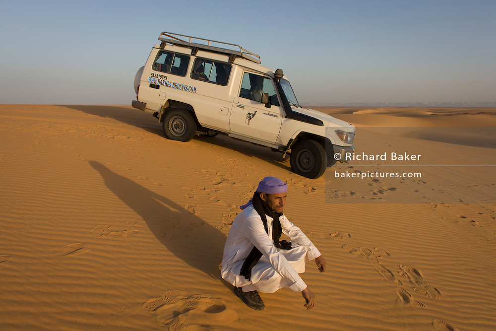 A Bedouin and his desert expedition 4x4 vehicle in sand dunes at al-Galamun, near Dahkla Oasis, Western Desert, Egypt. The past few decades have been difficult for traditional Bedouin culture due to changing surroundings and the establishment of new resort towns on the Red Sea coast, such as Sharm el-Sheikh. Bedouins in Egypt are facing a number of challenges: erosion of traditional values, unemployment, and various land issues. The Western Desert covers an area of some 700,000 km2, thereby accounting for around two-thirds of Egypt's total land area. Dakhla Oasis is one of the seven oases of Egypt's Western Desert (part of the Libyan Desert). It lies in the New Valley Governorate, 350 km (220 mi.) and measures approximately 80 km (50 mi) from east to west and 25 km (16 mi) from north to south.