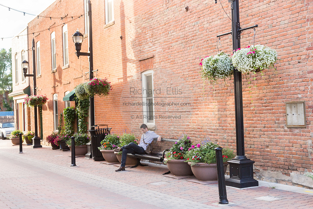 A man looks at his mobile phone in the Old Town historic shopping and restaurant district in Fort Collins, Colorado.