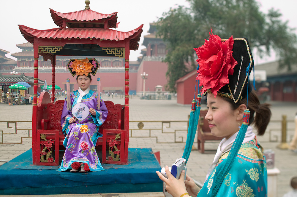 Asia, China, Beijing, Chinese tourists wear imperial era costumes while posing for souvenir snapshots at photo studio near the Gate of Heavenly Peace in the Forbidden City.