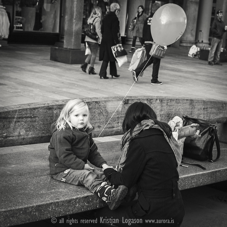 Girl with balloon sitting calmly on one of the stone benches at torgalmenningen in central Bergen while getting help from here mother