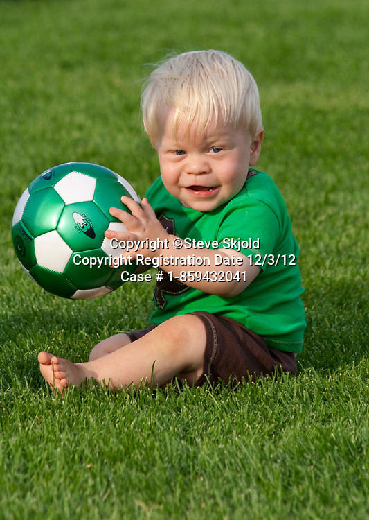 Rugged young toddler holding soccer ball on the field. Carondelet Field by Expo School St Paul Minnesota MN USA