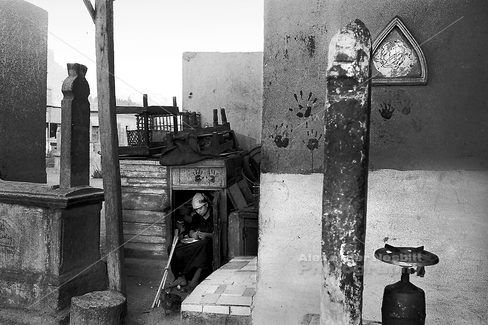 Cairo, Egypt, The City of the Dead, 2000 - Girl working in a make shift kitchen locker in her family compound among the grave markers.