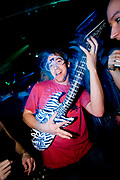 Raver in club with a blow-up guitar dancing to music,<br /> Club Class, Maidstone, Kent.