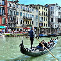 Gondola Rowing Along Grand Canal in Venice, Italy<br /> The gondola used to be a main form of transportation in Venice but today these black, flat-bottomed rowboats are primarily an iconic ride or ferry for tourists.  It takes years of extensive training, exams and an apprenticeship to become a professional gondolier and then they have to wait because the guild only issues 425 licenses.  The first woman was admitted in 2010.