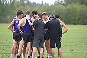 Washington Huskies assistant coach Chris Kwiatkowski (foreground) and head track and cross country coach Andy Powell (in grey cap) huddle with their team before the start of the men's 4 mile run at the UW/Seattle University Open race at Warren G. Magnuson Park., Friday, Aug. 30, 2019, in Seattle. (Paul Merca/Image of Sport)