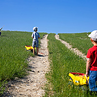 The Rev. William Johnson scans the hills for ground squirrels as his sons Quinten, 5, center, and Corban, 2, follow behind to collect the dead rodents in their Tonka trucks. The three were tracking down the rodents for a Father's Day gopher-hunting contest.