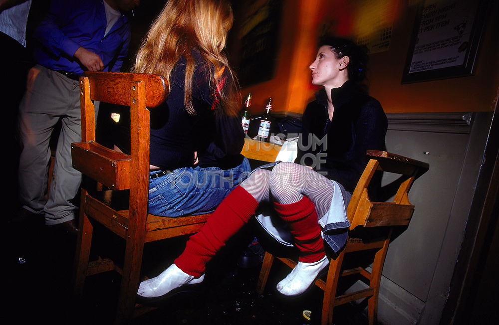 Two girls sat at a table talking one wearing red leg warmers at The Dog Star Brixton London April 2002