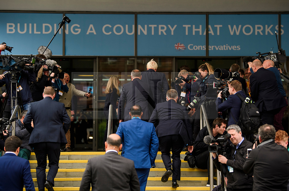 © Licensed to London News Pictures. 03/10/2017. Manchester, UK. British foreign secretary BORIS JOHNSON (centre) surrounded by media as he arrives at the conference hall to deliver his keynote speech on day three of the Conservative Party Conference. The four day event is expected to focus heavily on Brexit, with the British prime minister hoping to dampen rumours of a leadership challenge. Photo credit: Ben Cawthra/LNP