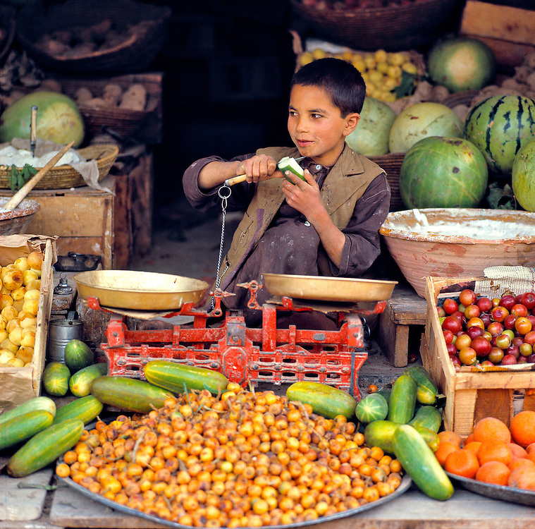 A young boy peels a cucumber in a produce stall in the bazaar at Mazar-i-Sharif, Afghanistan.