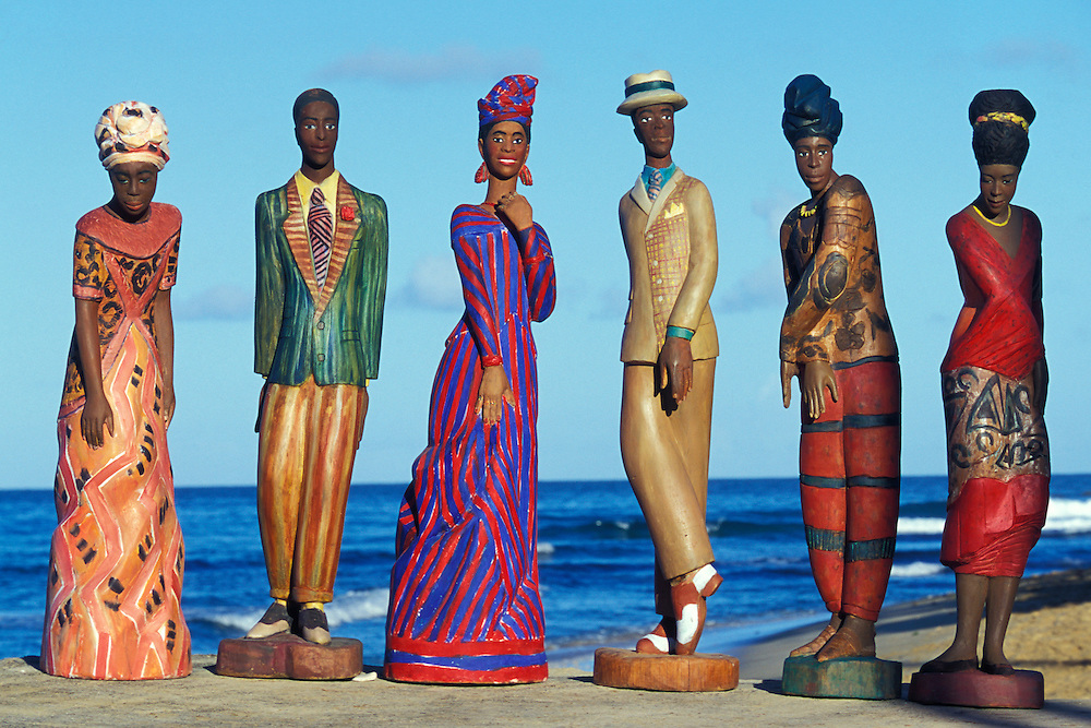 """Luise Kimme is a German sculptor who lives in Tobago since 1979. Her Sculpture Museum, locally called """"The Castle"""", overlooks the Mt. Irvine Golf Course with view of the Caribbean Sea. Her unique and  larger than life size Caribbean sculptures are made from oak, cedar, lime, cypress and bronze, depicting perfect portraits of the beautiful Tobagonians..I have photographed this amazing artist and her work since 1996. Together we produced a number of books and catalogues. She shares her self designed 'Castle' with her 8 dogs and 1 cat. They are often the subjects of Luise Kimme's work. More at www.luisekimme.com"""