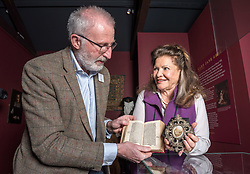 © Licensed to London News Pictures. 16/04/2018. Winchcombe, Gloucestershire, UK. Sudeley Castle's 'Royal Sudeley 1,000, Trials, Triumphs and Treasures'. Picture of DEREK MADDOCK, Sudeley Castle Archivist, holding a book with wife of Henry VIII Katherine Parr's formal signature, and LADY ASHCOMBE holding a lock of Katherine Parr's hair. Treasures from Sudeley Castle's 1,000 year history have gone on show in a new exhibition. Called 'Royal Sudeley 1,000, Trials, Triumphs and Treasures', the newly refurbished exhibition includes a collection of priceless objects and curiosities. The exhibition includes a one-of-a-kind, life-size glass-engraved portrait of Katherine Parr by critically acclaimed artist, John Hutton. The artwork was re-discovered during the refurbishment of a holiday cottage on the estate, where it had been for decades. Its importance has now been realised and so it has been brought into the exhibition collection. Numerous items of historic significance are also on display, such as a lock of Katherine Parr's hair, her prayer book and an intricate lace christening canopy believed to have been worked on by Anne Boleyn for the christening of her daughter, Elizabeth I. Sudeley was a royal residence, closely associated with some of the most famous English monarchs, including Edward IV, Richard III, Henry VIII, Lady Jane Grey, Katherine Parr, Elizabeth I and Charles I. The Castle was even home to a secret Queen of England, Eleanor Boteler, whose royal status was unknown for centuries. Photo credit: Simon Chapman/LNP