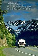 Alaska. Vehicles drive the Seward Highway, Chugach Mts in background.