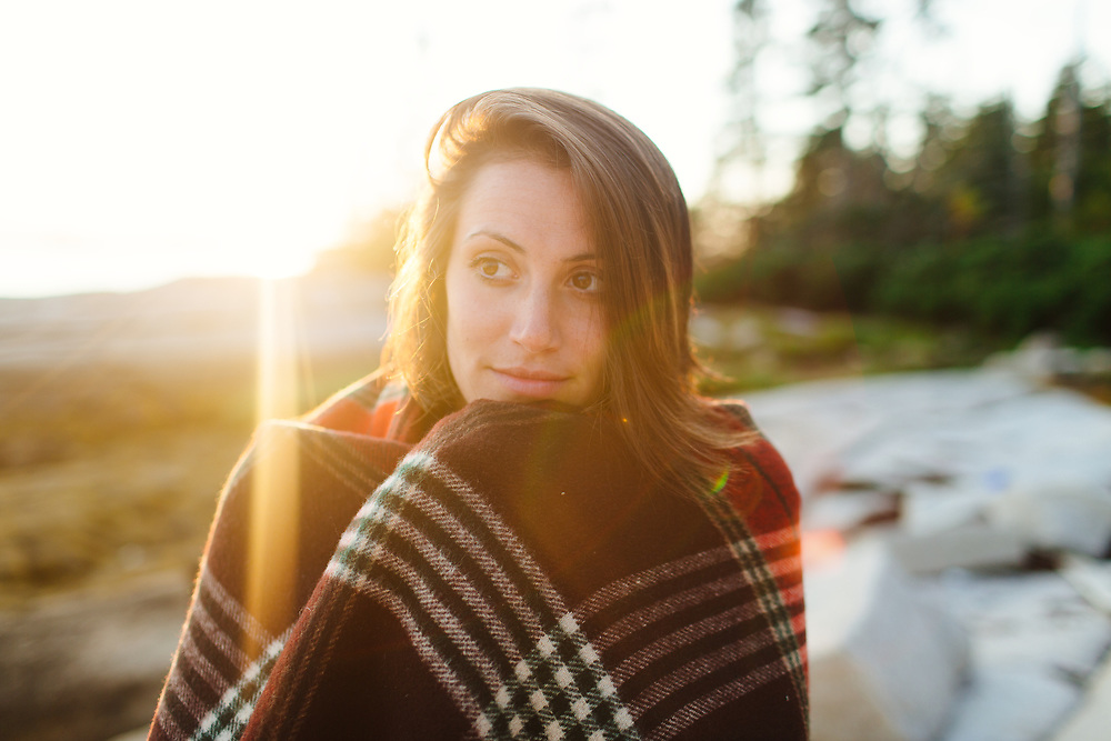 Woman Outdoors with Blanket, sun in background.
