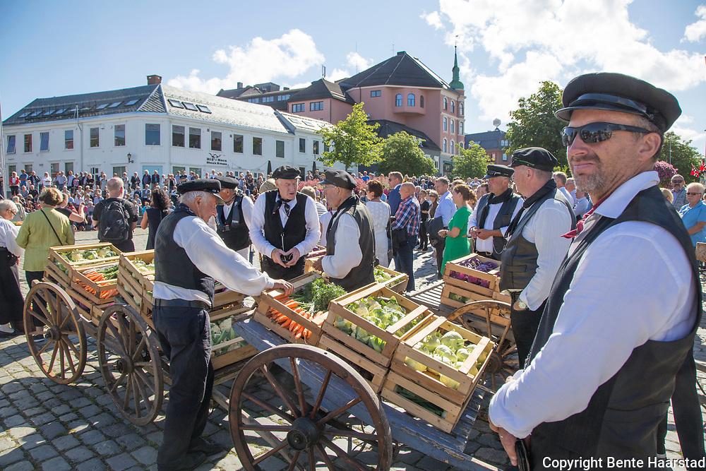 """Åpningen av matfestivalen i Trondheim (under Olavsfestdagene) i Ravnkloa. Tradisjonen tro blir roere, som kommer sjøveien fra Frosta, tatt imot i havna. Ravnkloa har vært fisketorg i mange hundre år, men her er det grønnsaker fra """"Trondheims kjøkkenhage"""" som lastes i land, for så å fraktes opp til festivalområdet rundt Torvet."""