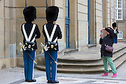 Tourist taking photograph of Royal Guard, in uniform at Royal Amalienborg Palace, Copenhagen, Denmark