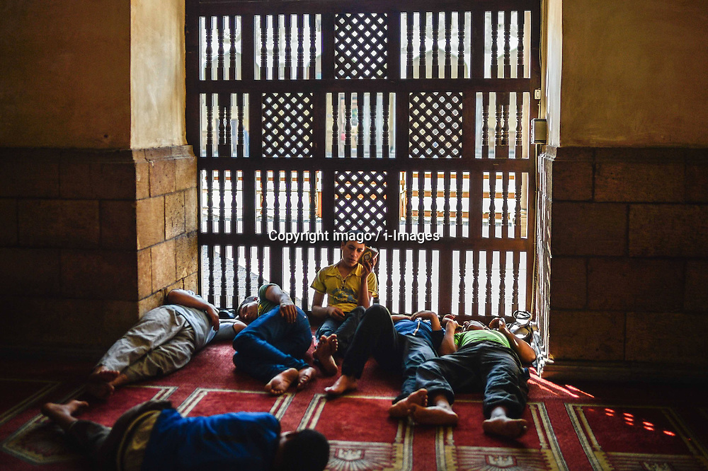 60103055  <br /> An Egyptian young man reads Quran while others sleep waiting for the time to break their fast at Al-Azhar Mosque on the first day of the holy month of Ramadan in Cairo, Egypt on Wednesday, July 10, 2013.<br /> Photo by imago / i-Images
