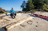 A female sea kayaker poses for a photo on Third Sister Island in the Canadian Gulf Islands   south of Ganges Harbor near Salt Spring Island, British Columbia, Canada.