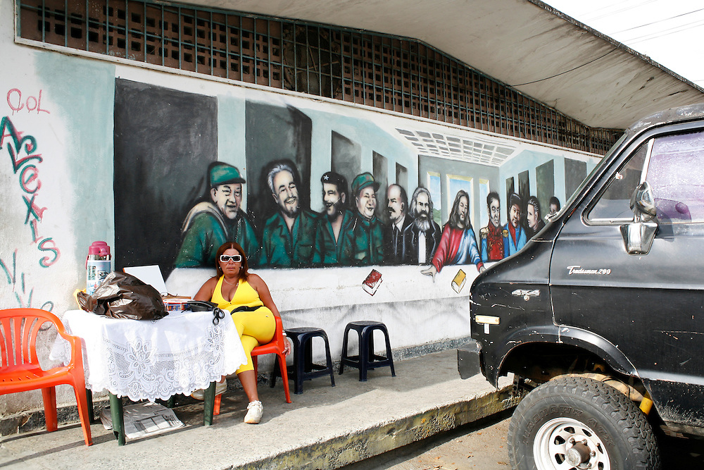 """A women in the 23 de Enero barrio in Caracas rents cell-phones underneath a mural of Venezuela's own version of """"the last supper""""."""