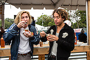 Queens, NY - October 2, 2016. Max Harwood (L) and Danny Miller of the band Lewis del Mar eating ceviche from Las Esquina del Camaron at The Feastival of Queens at The Meadows festival at Citi Field.