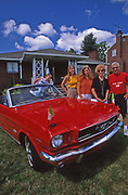 Family poses with classic Ford Mustang convertible, Alliquippa, PA, during patron saint parade day.