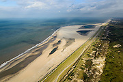 Nederland, Zuid-Holland, Gemeente Westland, 23-10-2013; Delflandse Kust ter hoogte van Ter Heijde en Monster, Scheveningen en Den Haag aan de horizon. Zandmotor, aanleg van kunstmatig schiereiland door het opspuiten van zand voor de kust. Wind, golven en stroming zullen het zand langs de kust verspreiden waardoor breder stranden en duinen ontstaan. De zandmotor is een experiment in het kader van kustonderhoud en kustverdediging. In de achtergrond de kassen van het Westland.<br /> Sand Engine, construction of artificial peninsula by the raising of sand for the coast of Ter Heijde (near the Hague, at the horizon). Wind, waves and currents will distribute the sand along the coast yielding wider beaches and dunes along the coastline. The Sand Engine is a experiment for coastal maintenance of coastal defense. In the background the Westland greenhouses.<br /> luchtfoto (toeslag op standard tarieven);<br /> aerial photo (additional fee required);<br /> copyright foto/photo Siebe Swart