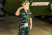 "11 JANUARY 2014 - BANGKOK, THAILAND: A boy dressed as a soldier salutes during Children's Day in Bangkok. The Royal Thai Army hosted a ""Children's Day"" event at the 2nd Cavalry King's Guard Division base in Bangkok. Children had an opportunity to look at military weapons, climb around on tanks, artillery pieces and helicopters and look at battlefield medical facilities. The Children's Day fair comes amidst political strife and concerns of a possible coup in Thailand. Earlier in the week, the Thai army announced that movements of armored vehicles through Bangkok were not in preparation of a coup, but were moving equipment into position for Children's Day.      PHOTO BY JACK KURTZ"