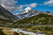 The peak of Aoraki / Mount Cook (3755 meters / 12,349 feet) rises majestically above the Third Swing Bridge on Hooker Valley Track, in Aoraki / Mount Cook National Park, Southern Alps, Canterbury region, South Island, New Zealand. In 1990, UNESCO honored Te Wahipounamu - South West New Zealand as a World Heritage Area.