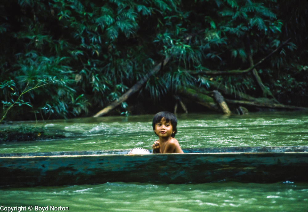 Iban people, youngster in a longboat on Skrang River, Sarawak, Borneo, Malaysia. The Iban were former headhunters.