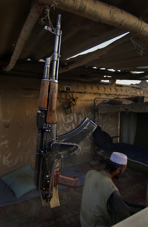 A Northern Alliance soldier's Kalashnikov rifle hangs at a guard shack outside of Bagram Air Base during afternoon prayers.