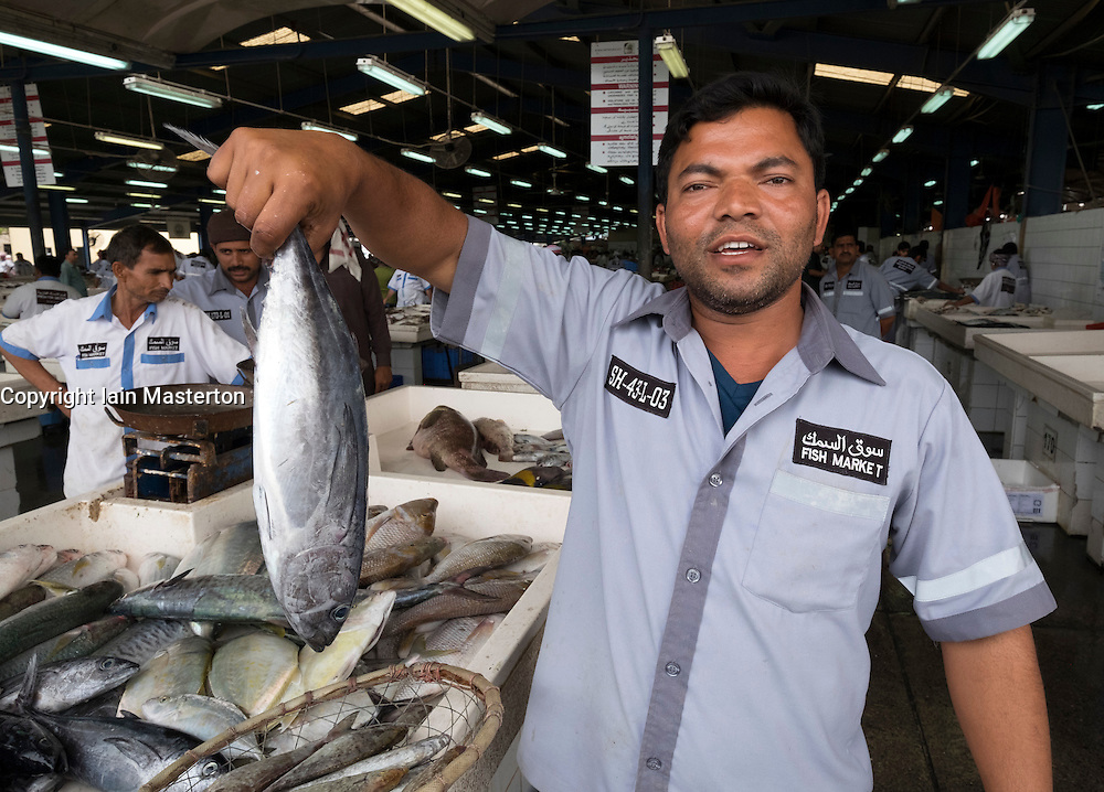 Fish market worker holding a fish for sale at Dubai fish market in Deira United Arab Emirates