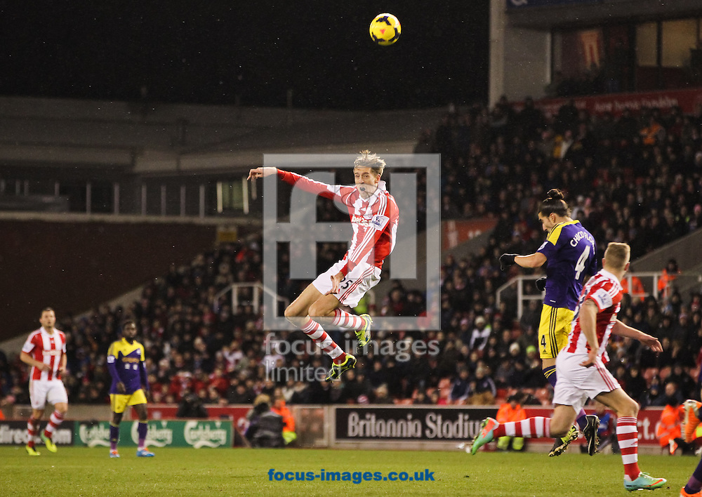Peter Crouch (centre) of Stoke City heads the ball on during the Barclays Premier League match at the Britannia Stadium, Stoke-on-Trent<br /> Picture by Tom Smith/Focus Images Ltd 07545141164<br /> 12/02/2014