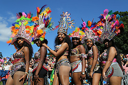 © Licensed to London News Pictures. 29/08/2016. Leeds, UK. Women wearing colourful feathers and beads pose at the Leeds West Indian Carnival in Leeds, West Yorkshire. First run in the 1960's, the Leeds West Indian Carnival is Europe's longest running authentic Caribbean carnival parade. Photo credit : Ian Hinchliffe/LNP