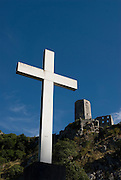 Big, Christian cross, fortress in background. Pocitelj. Bosnia. Eastern Europe.