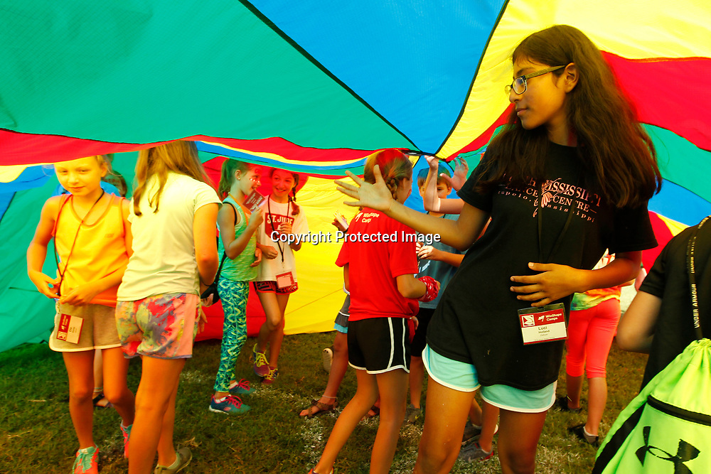 "Luci Holland, 11, of Tupelo, looks for her way out while playing the parachute game during the ""Connectreation"" time at WinShape Camp Wednesday morning at Harrisburg Baptist Church in Tupelo."