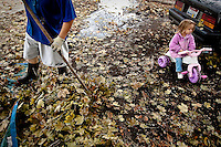 JEROME A. POLLOS/Press..Natalie Sweet, 3, sits on her tricycle while her father Kevin Sweet rakes leaves from their front yard Tuesday along Government Way in Coeur d'Alene.