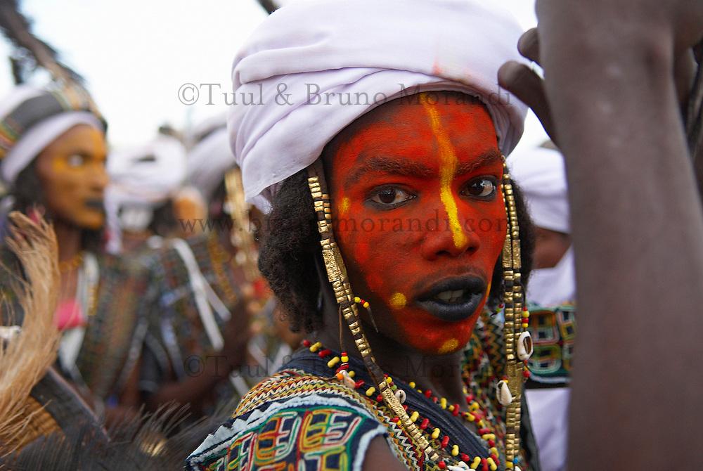 Niger. Gerewol, assemblee generale des Peuls Wadabee d Afrique de l'Ouest. Peul Bororo. Chaque annee pendant l'hivernage, les Peul Bororo se retrouvent apres un an de transhumances pour celebrer le Gerewol. Profondement animistes, la vie des Bororo est dictee par la beaute. Ce culte atteint son apotheose lors de cette fete originale ou seuls les hommes concourent. Apres des heures de preparation, ils se presentent en ligne, maquilles, pares de bijoux et de leur plus beaux atours. Ils chantent et dansent lentement ainsi, puis offrent aux femmes leurs sourires crispes et leurs yeux ecarquilles afin de mettre en avant l'esthetique de leur visage. Les jeunes filles Bororo se melent ensuite aux danseurs et choisissent les plus beaux. // Niger. A Wodaabe-Bororo man with his face painted for the annual Gerewol male beauty contest. Gerewol, general reunion of West Africa for the Wadabee Peuls (Bororo peul). Every year the Peuls are meeting after one year of transhumance to celebrate the Gerewol.