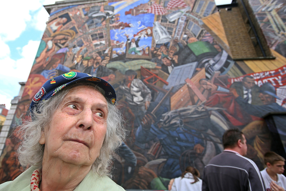 "Mrs Betty Papworth a veteran peace campaigner stands in front of the Cable Street mural on the 70th anniversary of ""The Battle of Cable Street"", Whitechapel, East London."