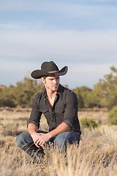 cowboy squatting in a field