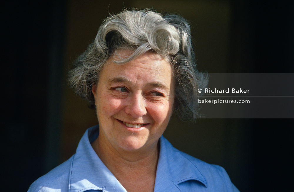 An English caucasian lady smiles at something of interest to the viewer's right. She is a wrinkled female in her sixties, a healthy person with her own original teeth and whose untidy hair is greying and whose skin is slightly tanned under a summer sun. She wears a blue shirt with a wide collar, fashionable in the 1980s (eighties) and has a bemused, attentive expression as if entertained by something of humour out of frame. This is someone's mother and grandmother, at an age when her hard-working life is nearly over and her pension is hopefully covering her everyday needs.
