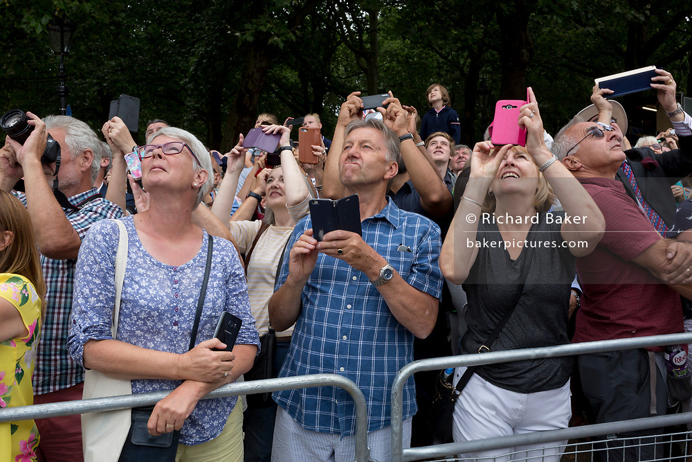 The public look upwards on the 100th anniversary of the Royal Air Force (RAF) and during a flypast of 100 aircraft formations representing Britain's air defence history which flew over central London, on 10th July 2018, in London, England.