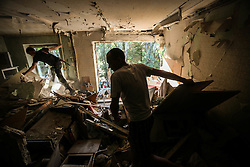 Locals search for victims in a damaged apartment in block of flats after Ukranian army shelling in downtown of Donetsk, Ukraine, 23 August 2014. Residential areas in several districts of Donetsk, including the central part of the city, suffered from artillery fire, five people was killed and 15 wounded, the press centre of Donetsk city Council reported.