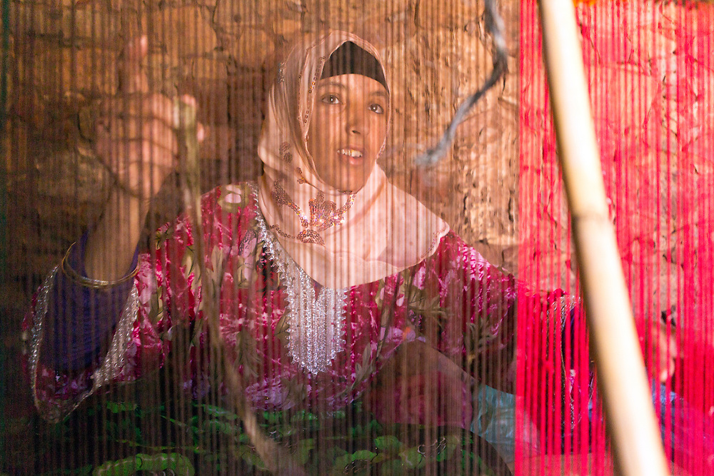 Portrait of key keeper Hassan's wife weaving a carpet using a traditional loom, Taliouine province of the Souss Massa Draa, Southern Morocco, 2016-05-25. <br />