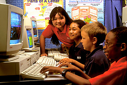 Stock photo of four children working on a computer in the classroom