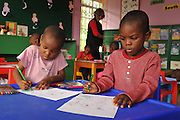 Kayise and Jabulani colouring in at pre-school.<br /> [For more information about the centre visit www.sandraleecentre.org]