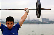 Shi Lung town Sports Academy for Weightlifters.Wang Wubing, 19, trains by the river with factories in the background.
