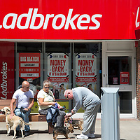 Bognor Regis, Sussex. People with dogs outside Ladbrokes betting shop.