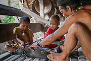 Mentawai indigenous man with kids killing a piglet (Indonesia).