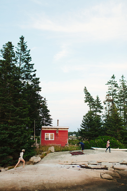 Women in front of red cabin, outdoors.